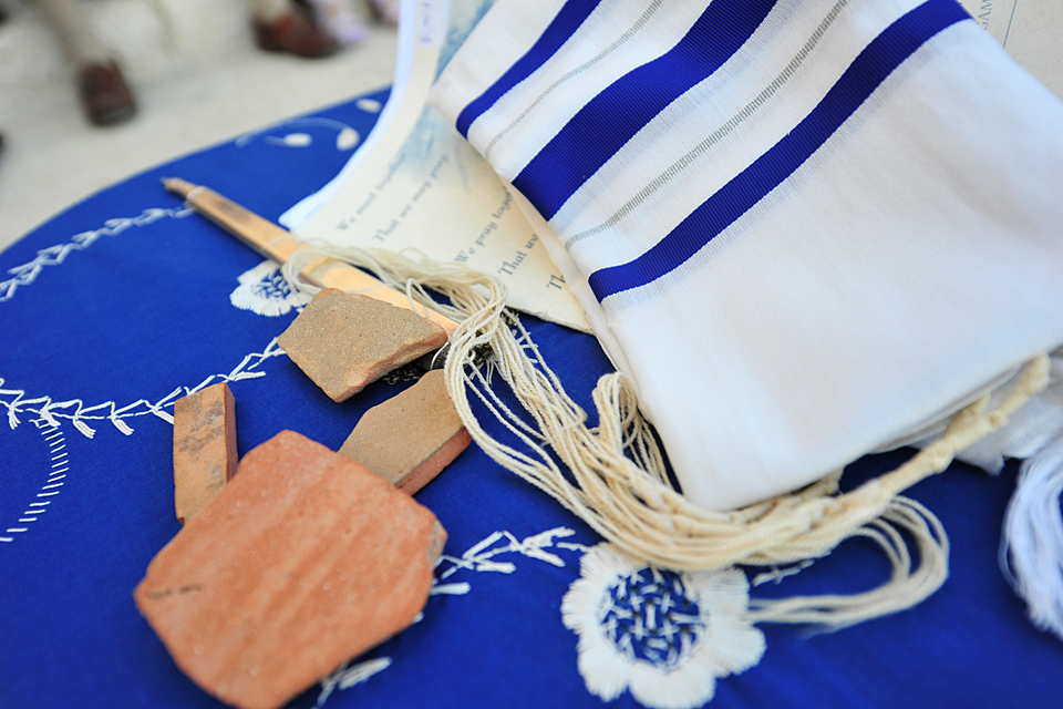 Ancient pottery pieces from Israel rest on a Jewish prayer shawl.