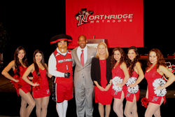 Matty, members of the Northridge Dance Team, Brandon Martin and President Dianne F. Harrison on stage in front of an athletics banner.