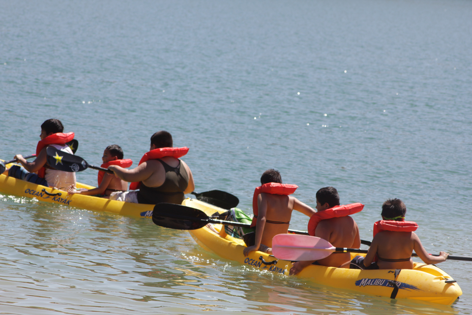 A group of children paddling kayaks.