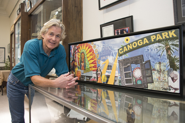 Color image of Finney leaning against a sign with the words Canoga Park